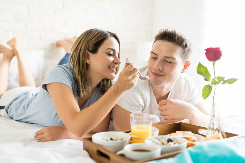 在早餐期间的妇女哺养的男朋友在床上 免版税图库摄影