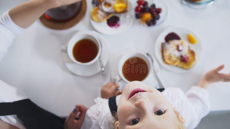 在早餐期间,小女孩顶视图喝茶和查寻 图库摄影