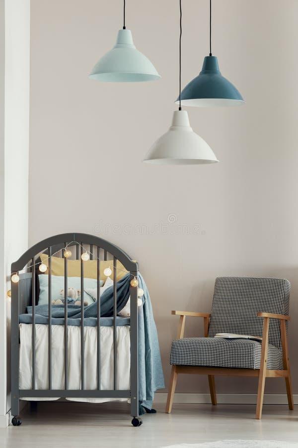 在时兴的斯堪的纳维亚婴孩卧室内部的灰色小儿床 免版税库存图片