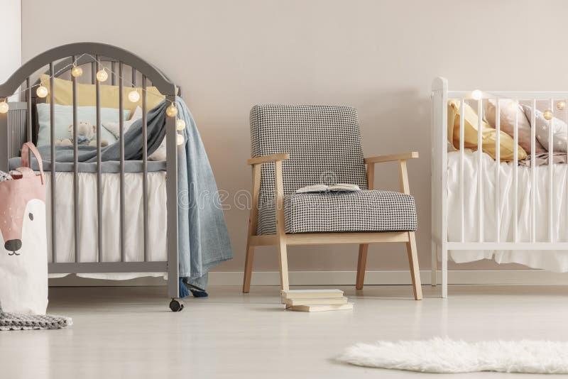 在时兴的斯堪的纳维亚婴孩卧室内部的灰色木小儿床 图库摄影