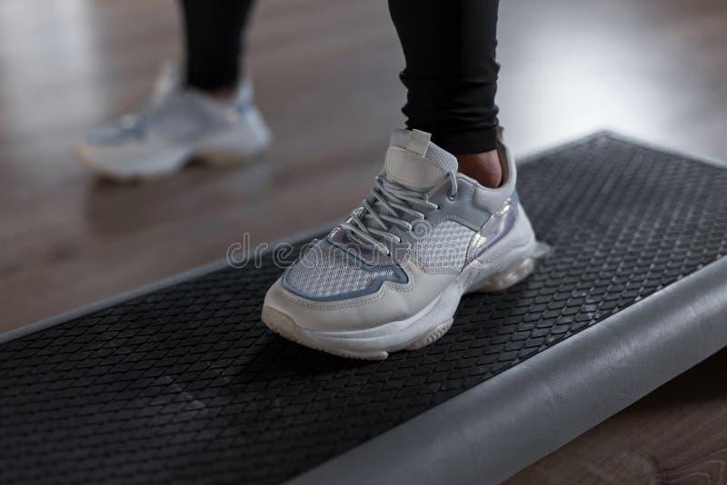 在时兴的白色运动鞋的妇女的腿在健身房的步平台站立 年轻女人在一间现代健身房行使 免版税库存图片