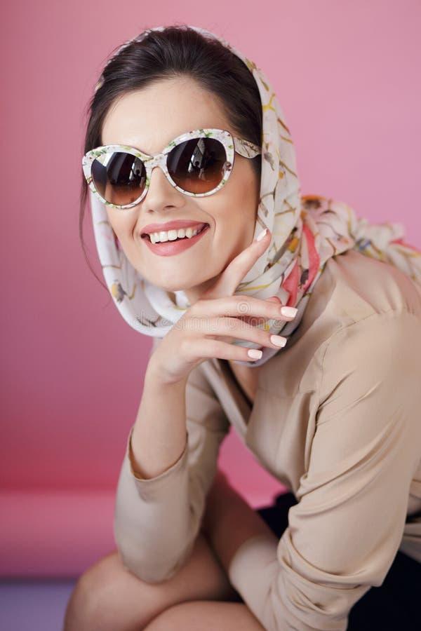在时兴的镜片和精美丝绸围巾的快乐的美女耳环,在桃红色背景 免版税图库摄影