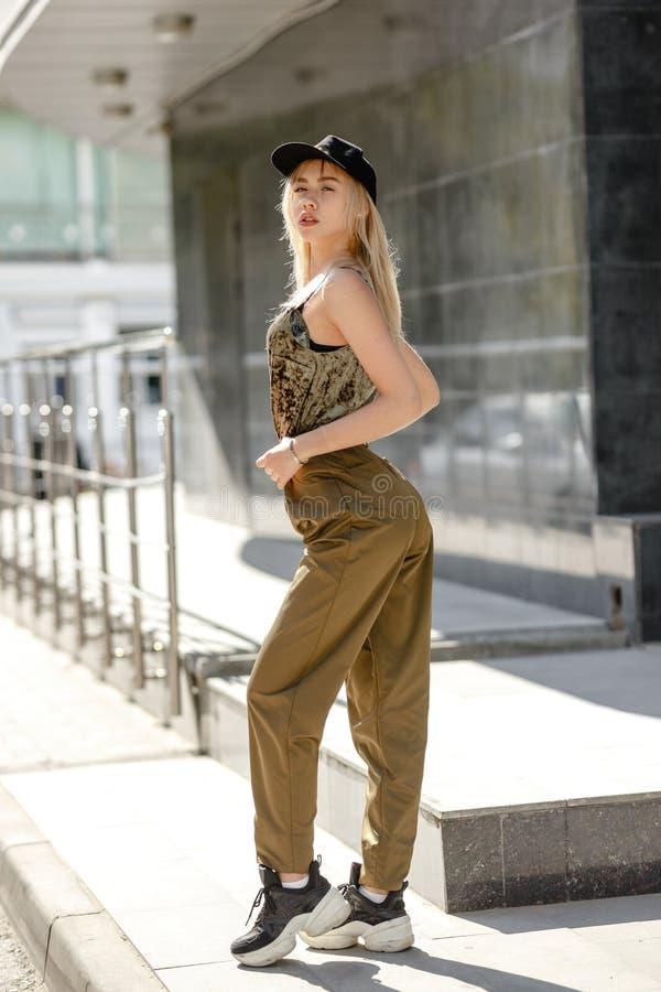在时兴的长裤和顶面卡其色的颜色和黑盖帽打扮的年轻白肤金发的女孩在顶头姿势在街道 免版税库存图片