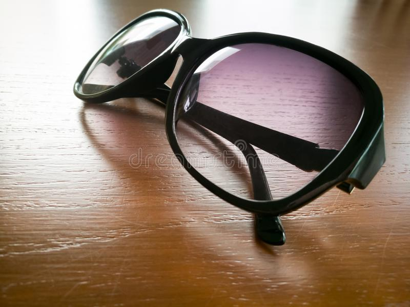 在时尚太阳镜下曝光在木桌上的 库存图片