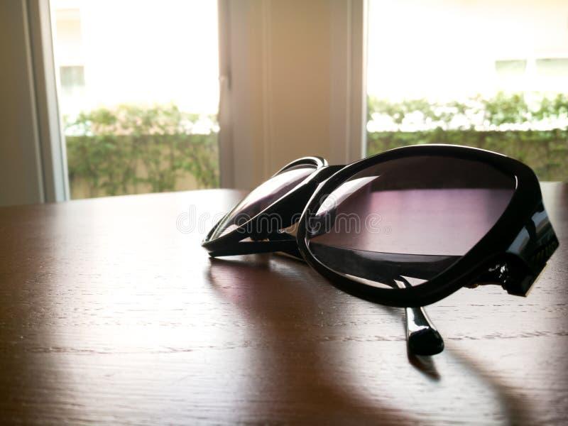 在时尚太阳镜下曝光在木桌上的 库存照片