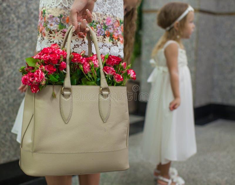 在时尚妇女的袋子的小红色迷人的玫瑰 库存照片