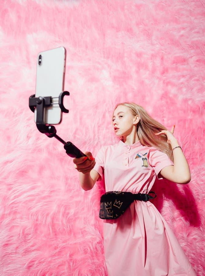 在时尚桃红色礼服打扮的年轻俏丽的女孩博客作者在桃红色毛皮墙壁背景做一selfie在展示的 免版税库存图片