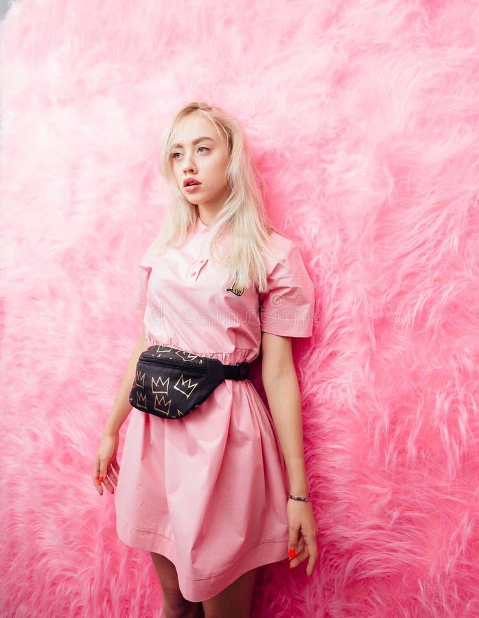 在时尚桃红色礼服打扮的年轻美丽的白肤金发的女孩在桃红色毛皮墙壁背景摆在展示屋子 库存图片