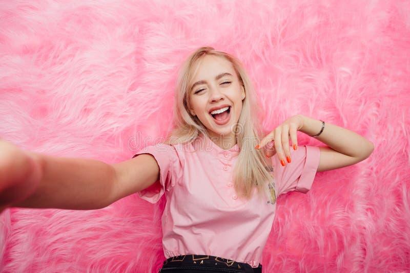 在时尚桃红色礼服打扮的滑稽的少女博客作者采取在她的智能手机的一selfie在桃红色毛皮背景  库存照片