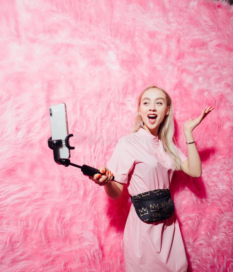 在时尚桃红色礼服打扮的美丽的少女博客作者在桃红色毛皮墙壁背景做一selfie在展示的 免版税库存照片