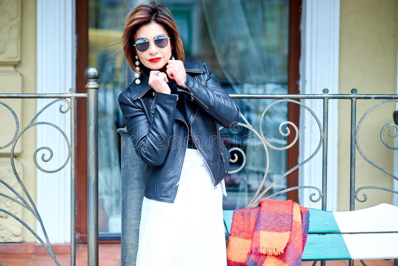 在时尚的玻璃和室外黑的皮夹克的时装模特儿 免版税图库摄影