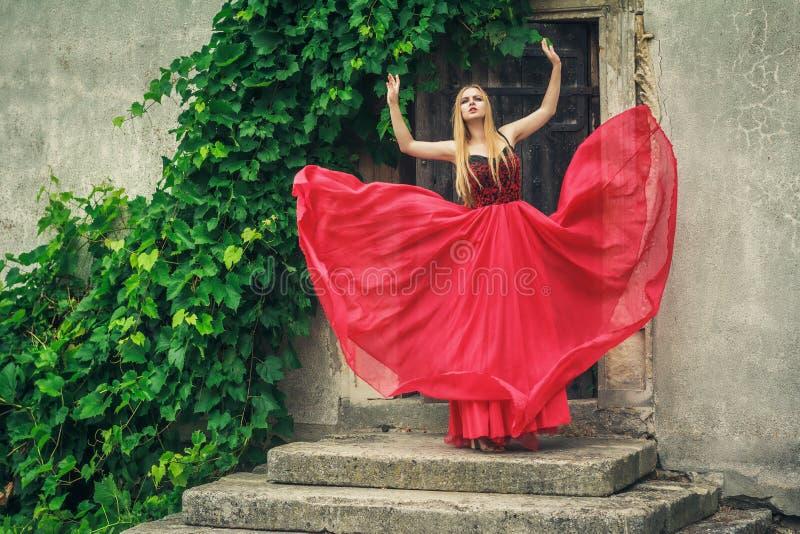 在时尚红色礼服的美好的少妇跳舞 库存照片
