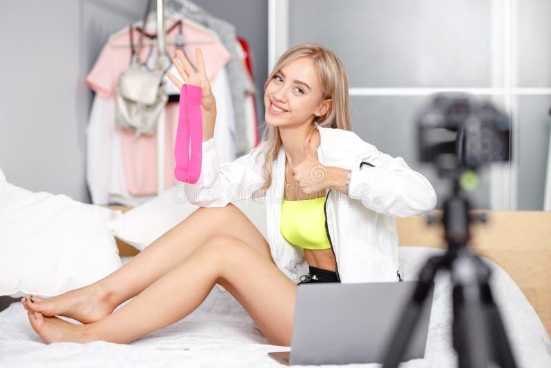 在时装打扮的俏丽的少女博客作者为给被摄制坐与的床做广告 免版税库存照片
