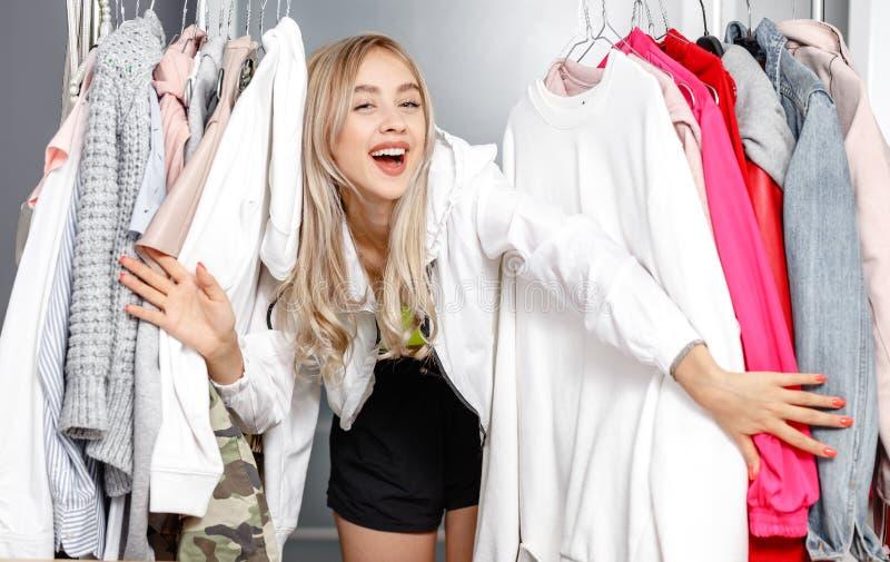 在时装打扮的滑稽的少女博客作者站立在垂悬在衣橱的一个挂衣架的衣裳之间 图库摄影