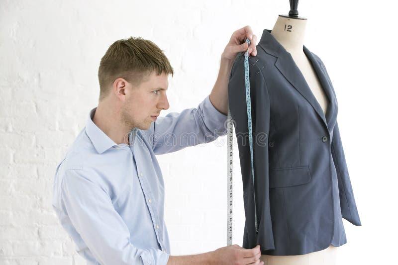 在时装模特的裁缝测量的衣服在演播室 图库摄影