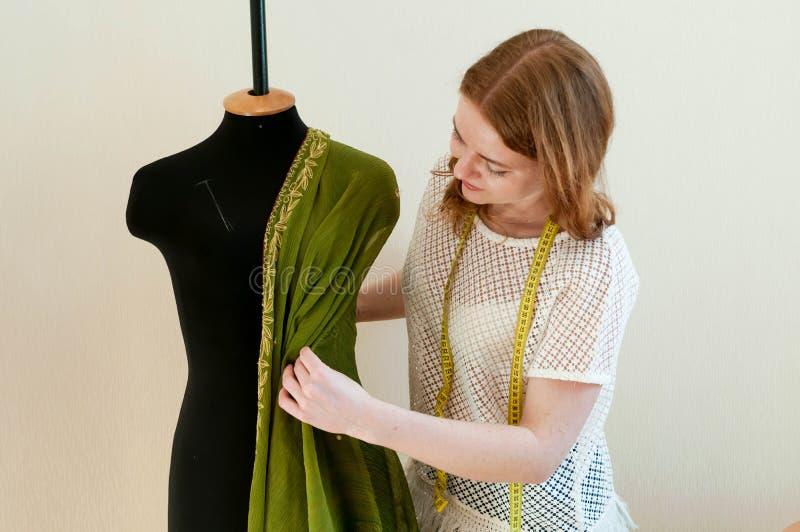 在时装模特附近的裁缝身分和垂悬布料在白色的缝合的演播室 免版税库存照片