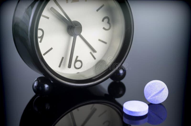 在时钟旁边的蓝色药片 图库摄影