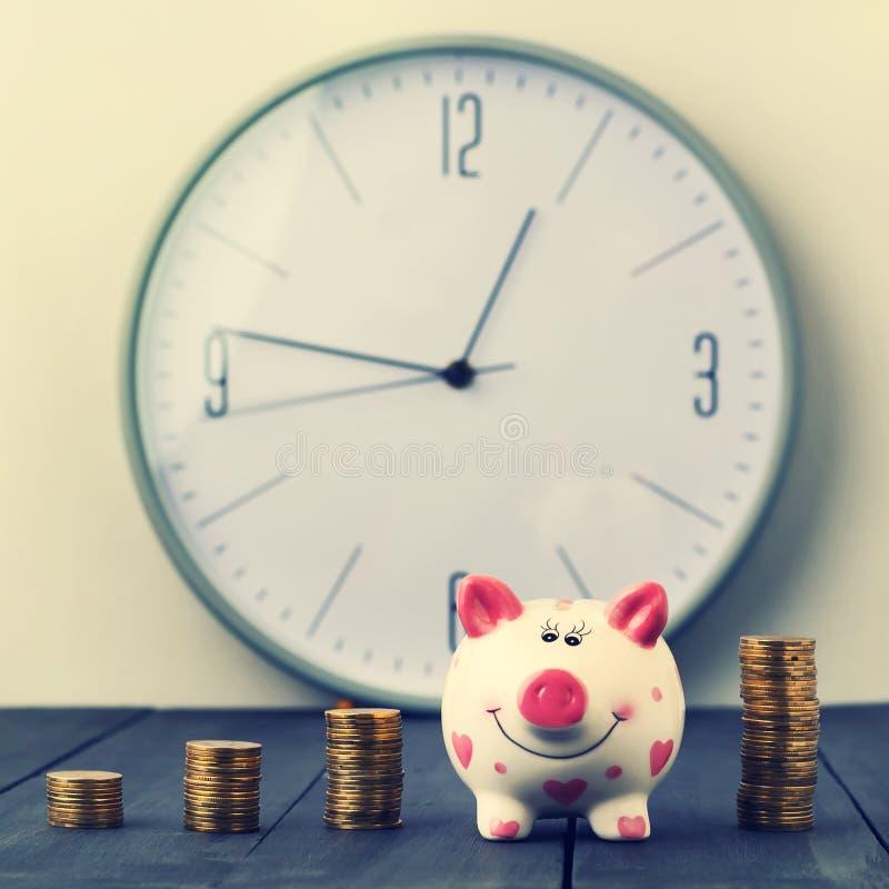 在时钟背景的存钱罐和塔硬币  复制空间 免版税图库摄影