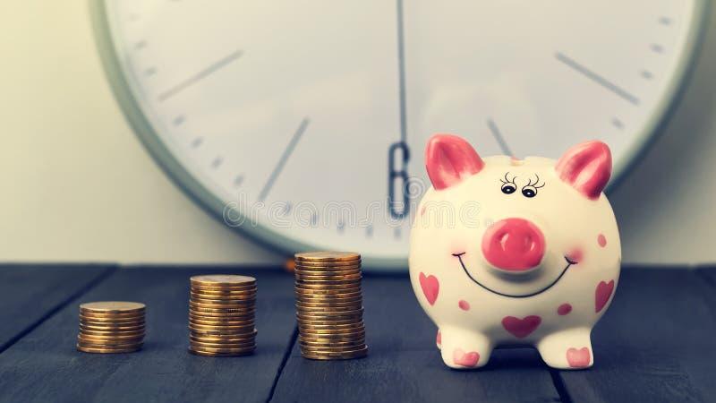 在时钟背景的存钱罐和塔硬币  复制空间 免版税库存照片
