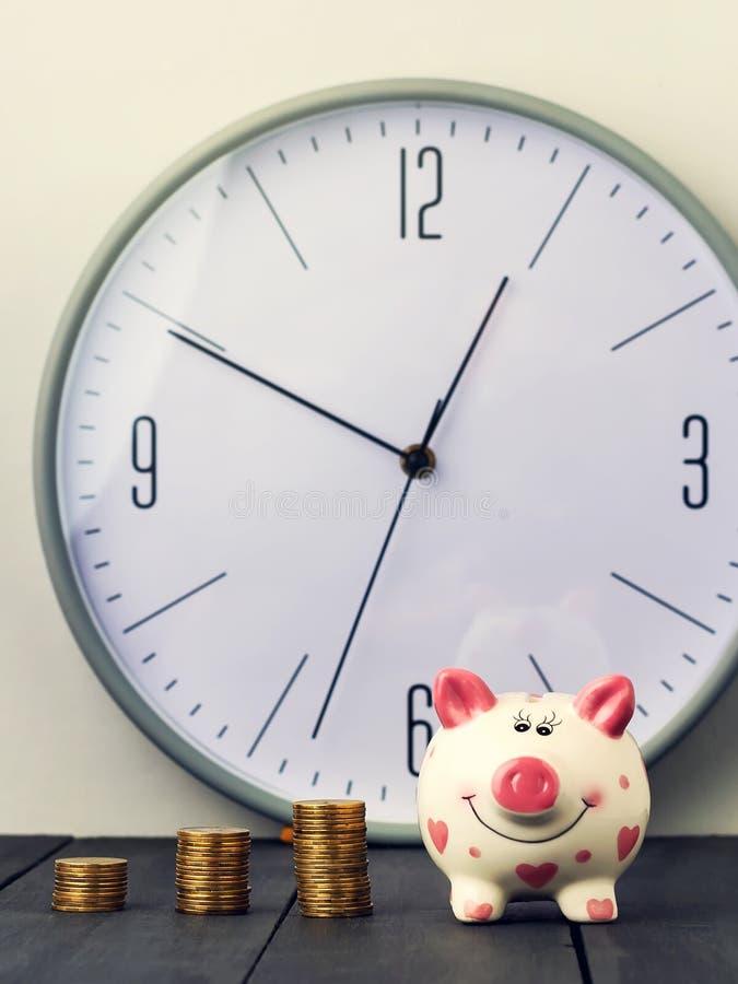 在时钟背景的存钱罐和塔硬币  复制空间 库存图片