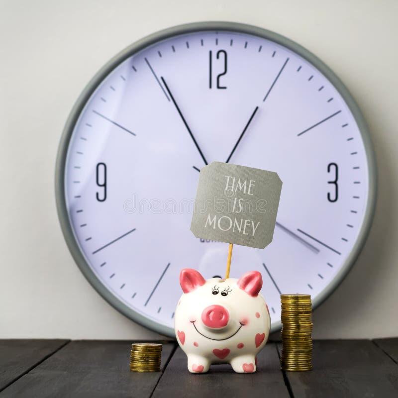 在时钟背景的存钱罐和塔硬币  题字时间是金钱 复制空间 免版税库存照片