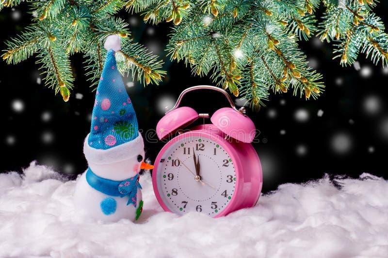 在时钟附近的玩具雪人在圣诞树附近的除夕在snowfall_期间 免版税库存图片