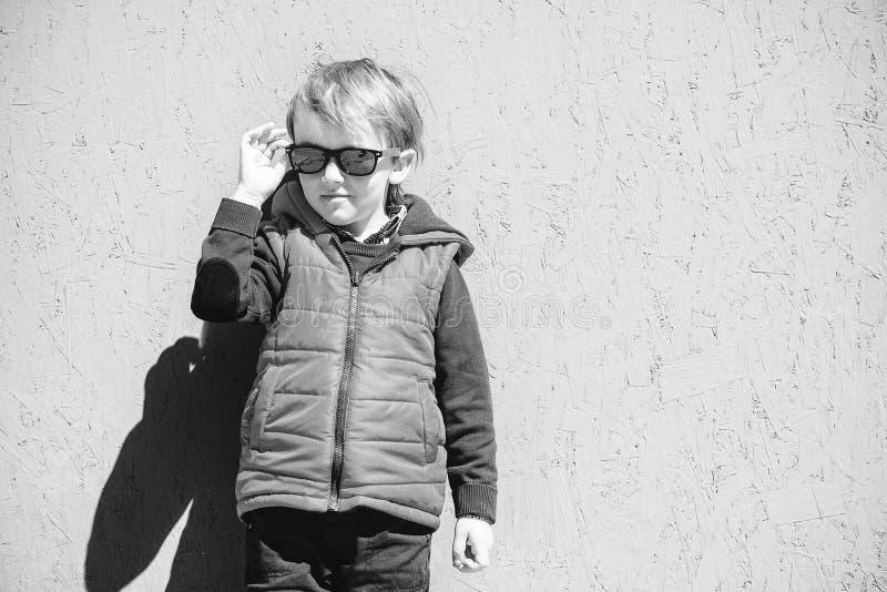 在时髦太阳镜的时髦的孩子 塑造孩子 红色夹克身分的逗人喜爱的矮小的blondy男孩在灰色墙壁户外在好日子 免版税图库摄影