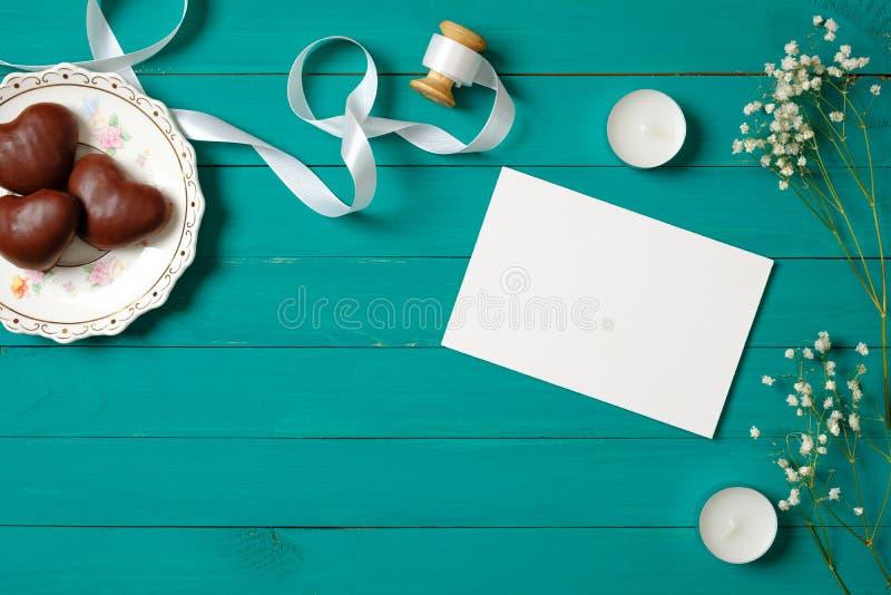在时髦的妇女的书桌上的空白的婚姻的请帖在绿色木背景 平的被放置的构成,顶视图,在头顶上 免版税库存图片