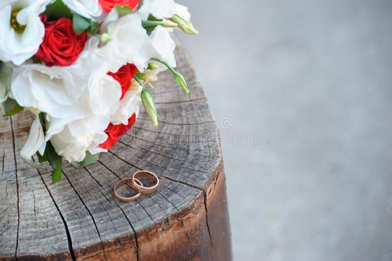 在时髦的婚礼花束附近的婚戒在木树桩 免版税库存照片