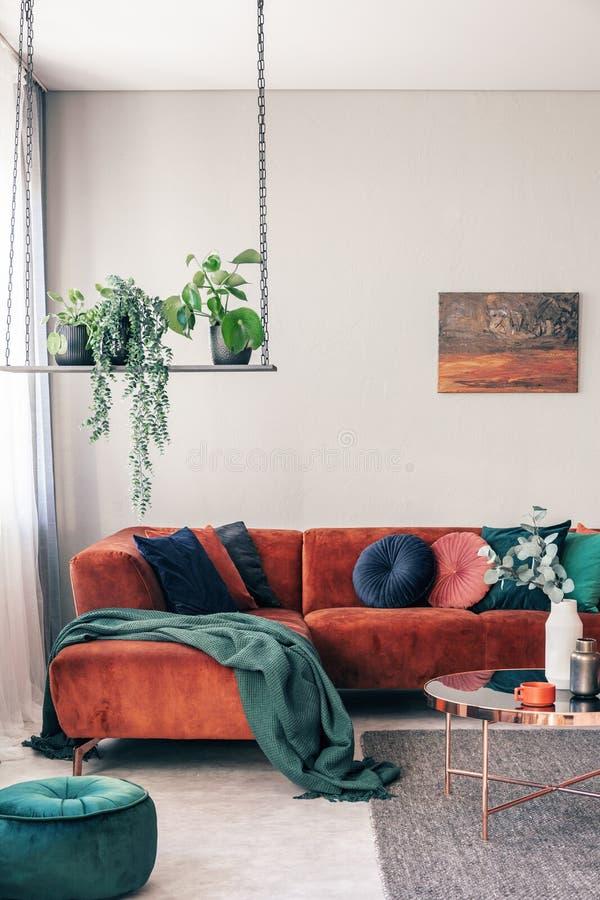 在时髦的摇摆的绿色花在与壁角沙发的优等的客厅内部有枕头的 免版税图库摄影