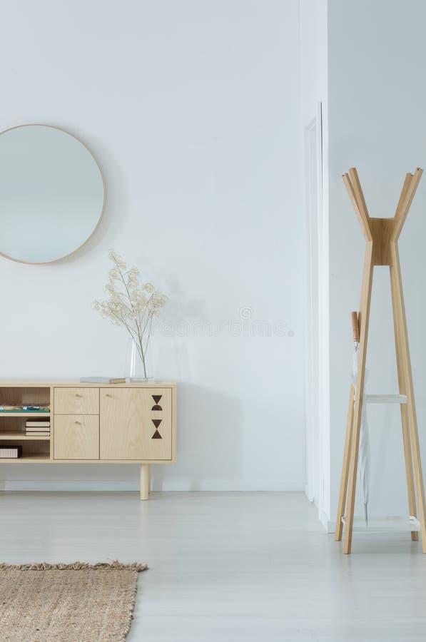 在时髦的木碗柜上的镜子有玻璃花瓶和花的对此,现代晒衣架在白色大厅的角落 库存照片