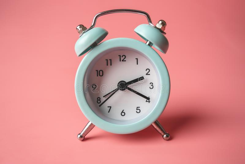 在时髦的桃红色背景的蓝色模式金属闹钟 时间的概念在淡色的 图库摄影