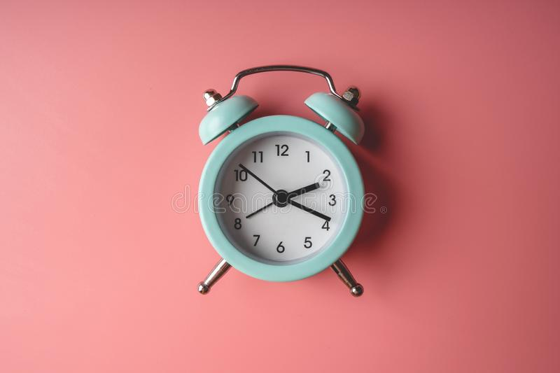 在时髦的桃红色背景的蓝色模式金属闹钟 时间的概念在淡色的 免版税库存照片