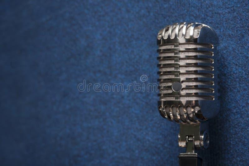 在时髦的深蓝难看的东西葡萄酒背景纹理的一个专业发光的现代动态演播室声音话筒 免版税库存图片