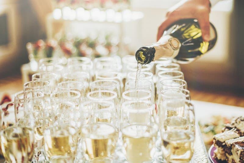 在时髦的玻璃的侍者倾吐的香槟在豪华婚礼关于 免版税库存图片