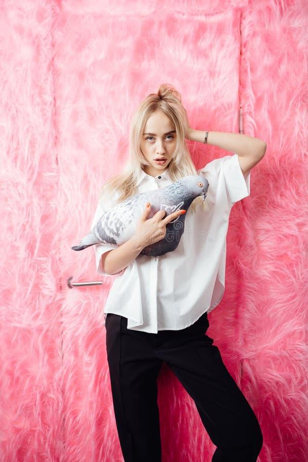 在时髦的白色衬衫和黑长裤姿势打扮的少女博客作者与与一个软的玩具以鸽子的形式 免版税图库摄影