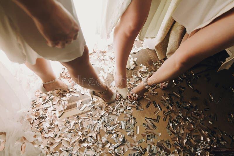 在时髦的白色鞋子的女孩腿,站立在金子和银色五彩纸屑,新娘闺房早晨党在婚礼前 图库摄影