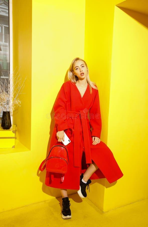 在时髦的红色外套打扮的美丽的少女博客作者在黄色墙壁背景摆在展示屋子 免版税库存图片