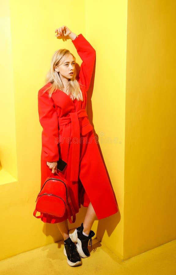在时髦的红色外套打扮的美丽的少女博客作者在黄色墙壁背景摆在展示屋子 库存照片