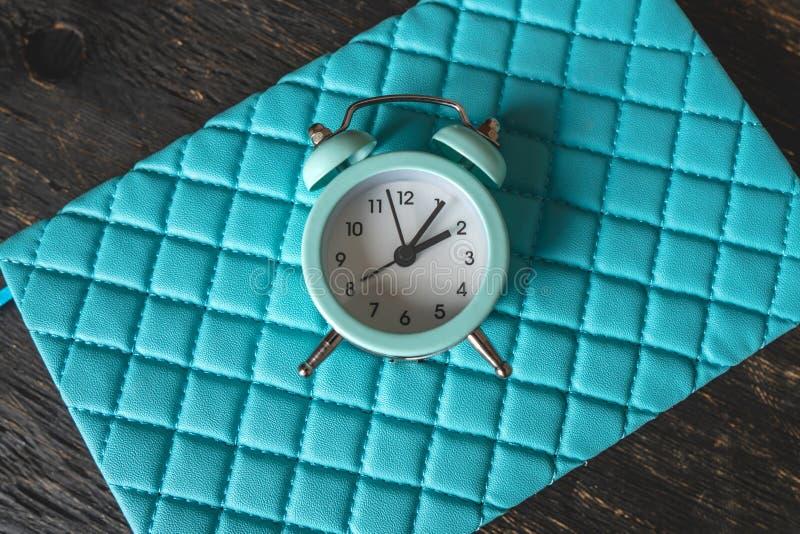 在时髦的蓝色背景的蓝色模式金属闹钟 时间的概念在柔和的淡色彩和深色的 库存图片