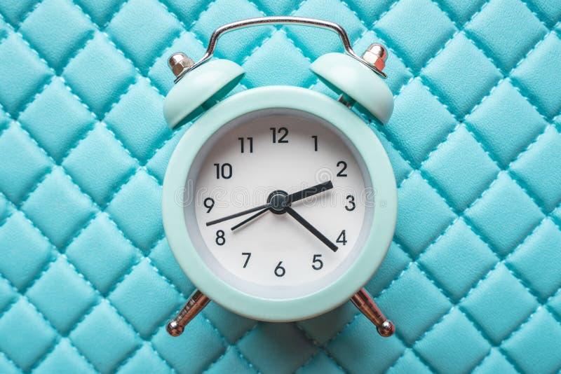 在时髦的蓝色背景的蓝色模式金属闹钟 时间的概念在淡色的 库存照片