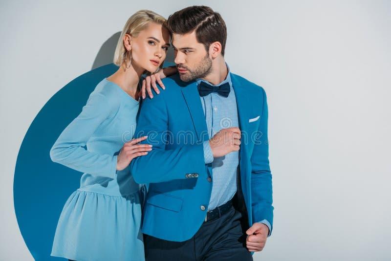 在时髦的蓝色衣服的美好的一起站立在开口的夫妇和礼服 图库摄影