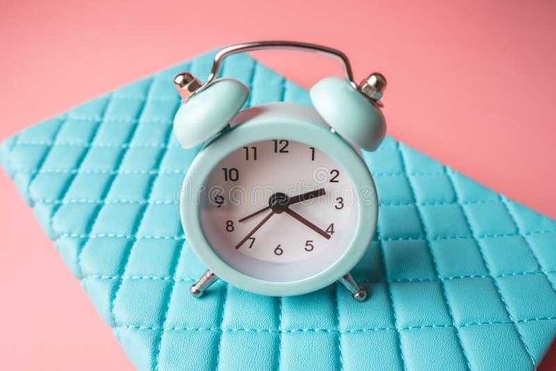 在时髦的青桃红色背景的蓝色模式金属闹钟 时间的概念在淡色的 库存图片