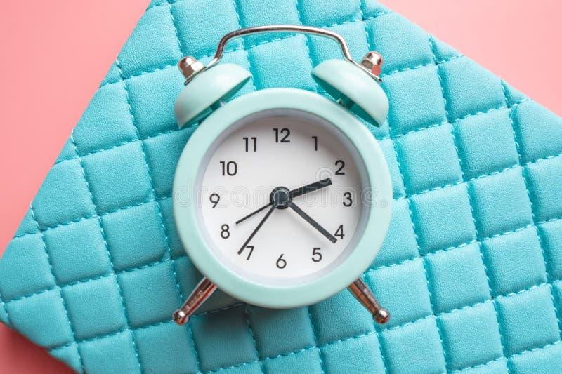 在时髦的青桃红色背景的蓝色模式金属闹钟 时间的概念在淡色的 库存照片