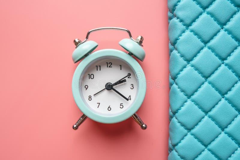 在时髦的青桃红色背景的蓝色模式金属闹钟 时间的概念在淡色的 免版税库存图片