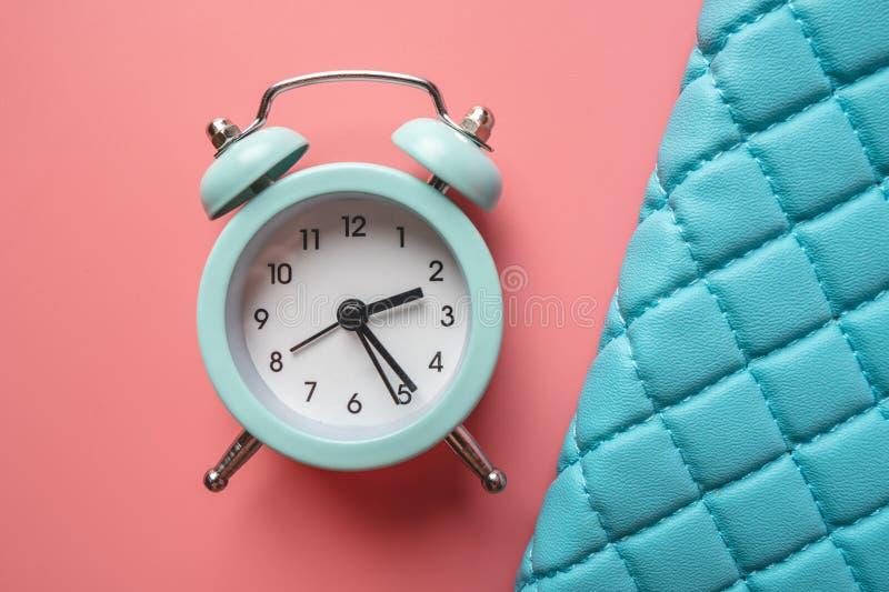 在时髦的青桃红色背景的蓝色模式金属闹钟 时间的概念在淡色的 免版税库存照片