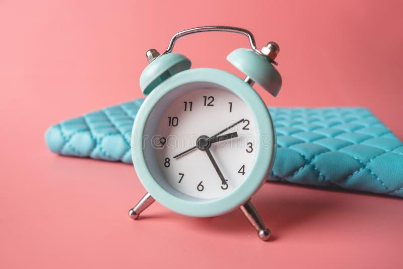 在时髦的青桃红色背景的蓝色模式金属闹钟 时间的概念在淡色的 图库摄影