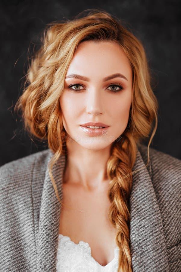在时髦的黑暗的大衣和白色礼服的美好的微笑的白肤金发的妇女模型 免版税库存图片