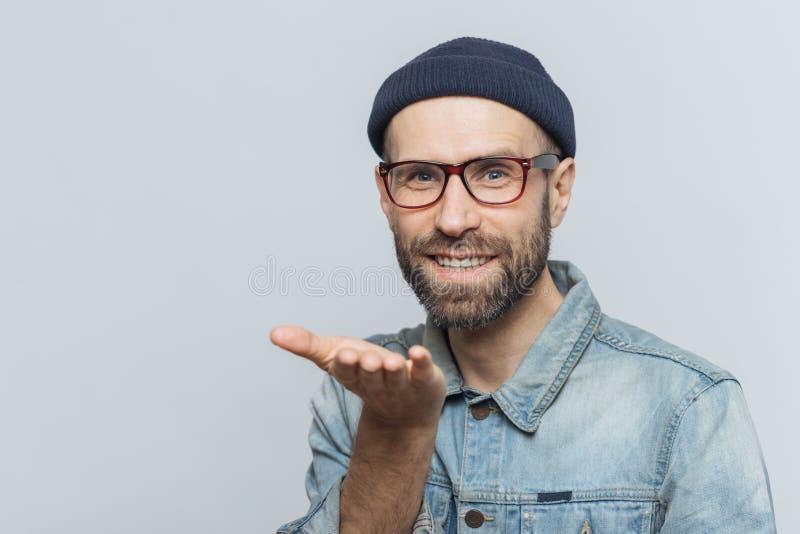 在时髦eyewear的高兴的有胡子的男性表现出他的爱,显示ai 库存照片