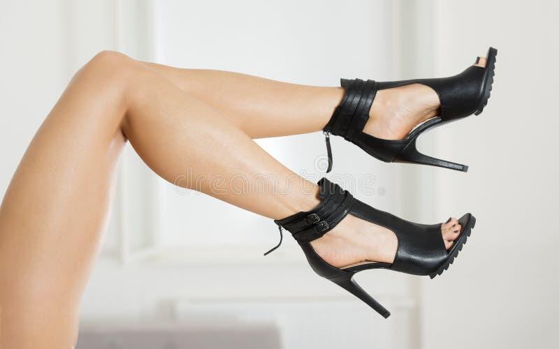 在时兴的高跟鞋鞋子的长和性感的腿 免版税库存照片